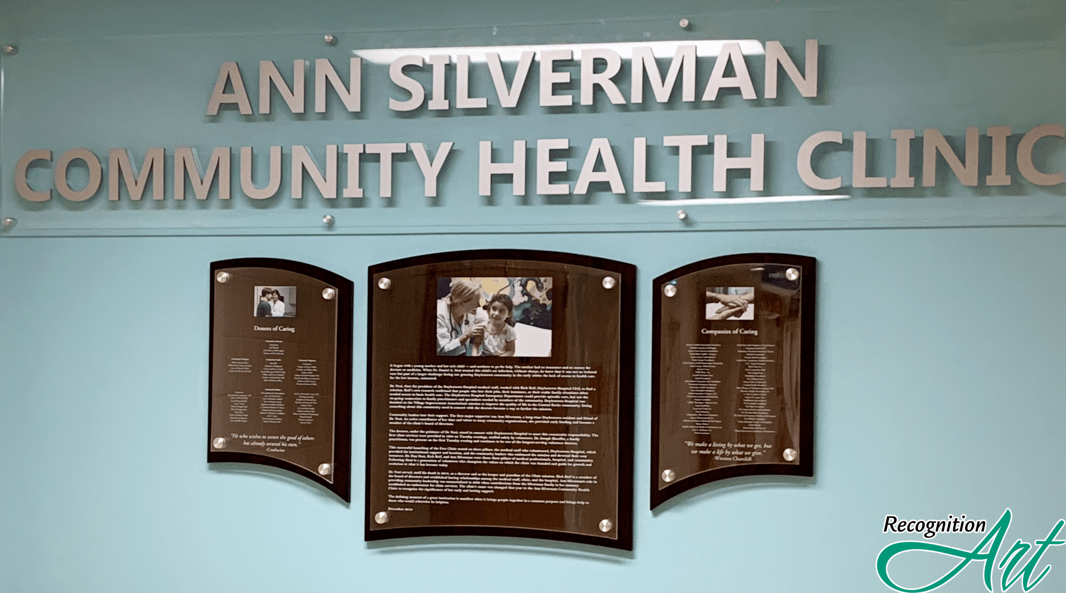 Acrylic header with metal letters that says Ann Silverman Community Health Clinic with a wood backer display with acrylic held by standoffs that display donors