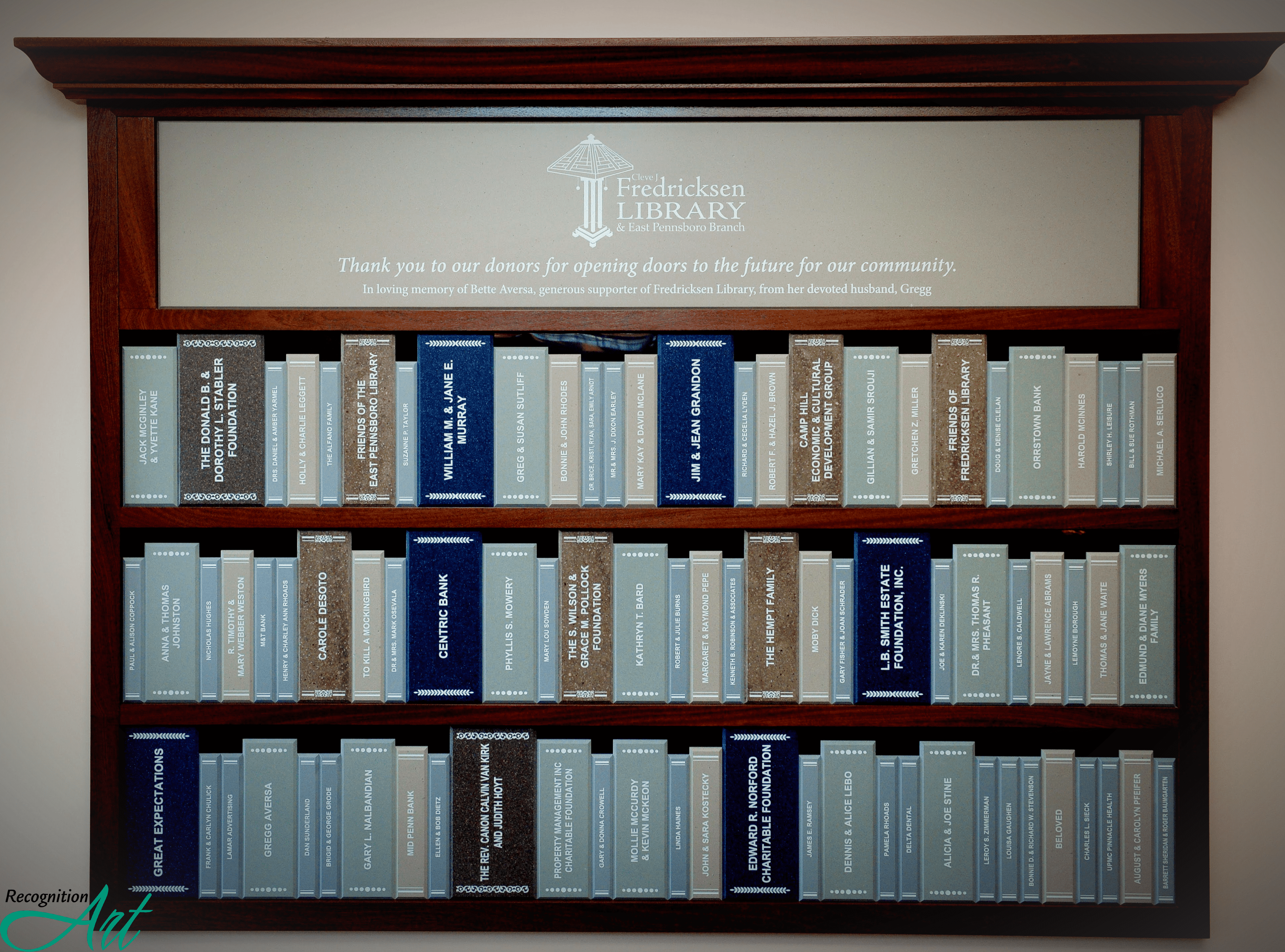 Donor wall made to look like a bookshelf with different sized book spines made of Corian engraved with donor names.
