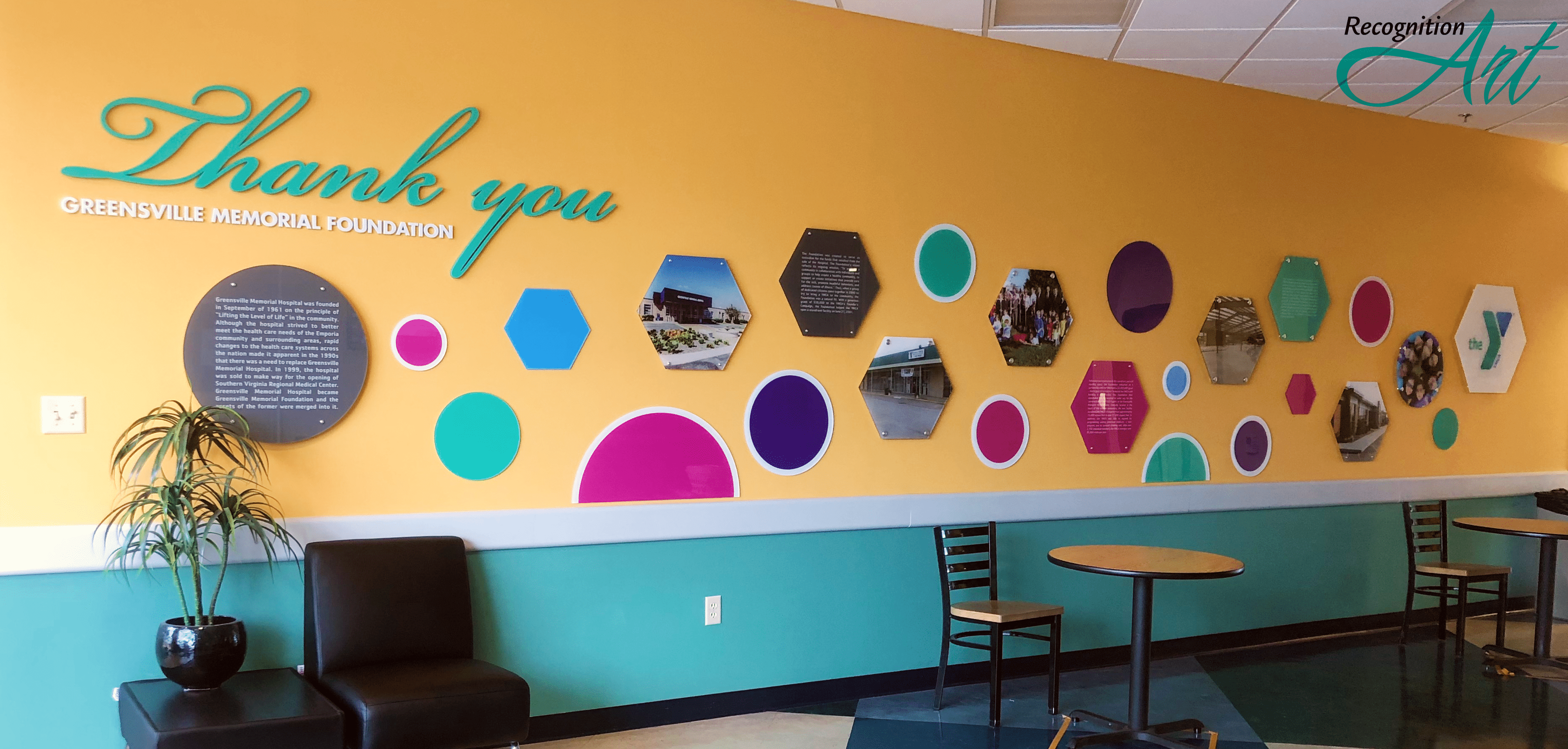 A donor wall made of pink, blue, green and purple acrylic circles and hexagons describing the journey of the Emporia-Greensville YMCA